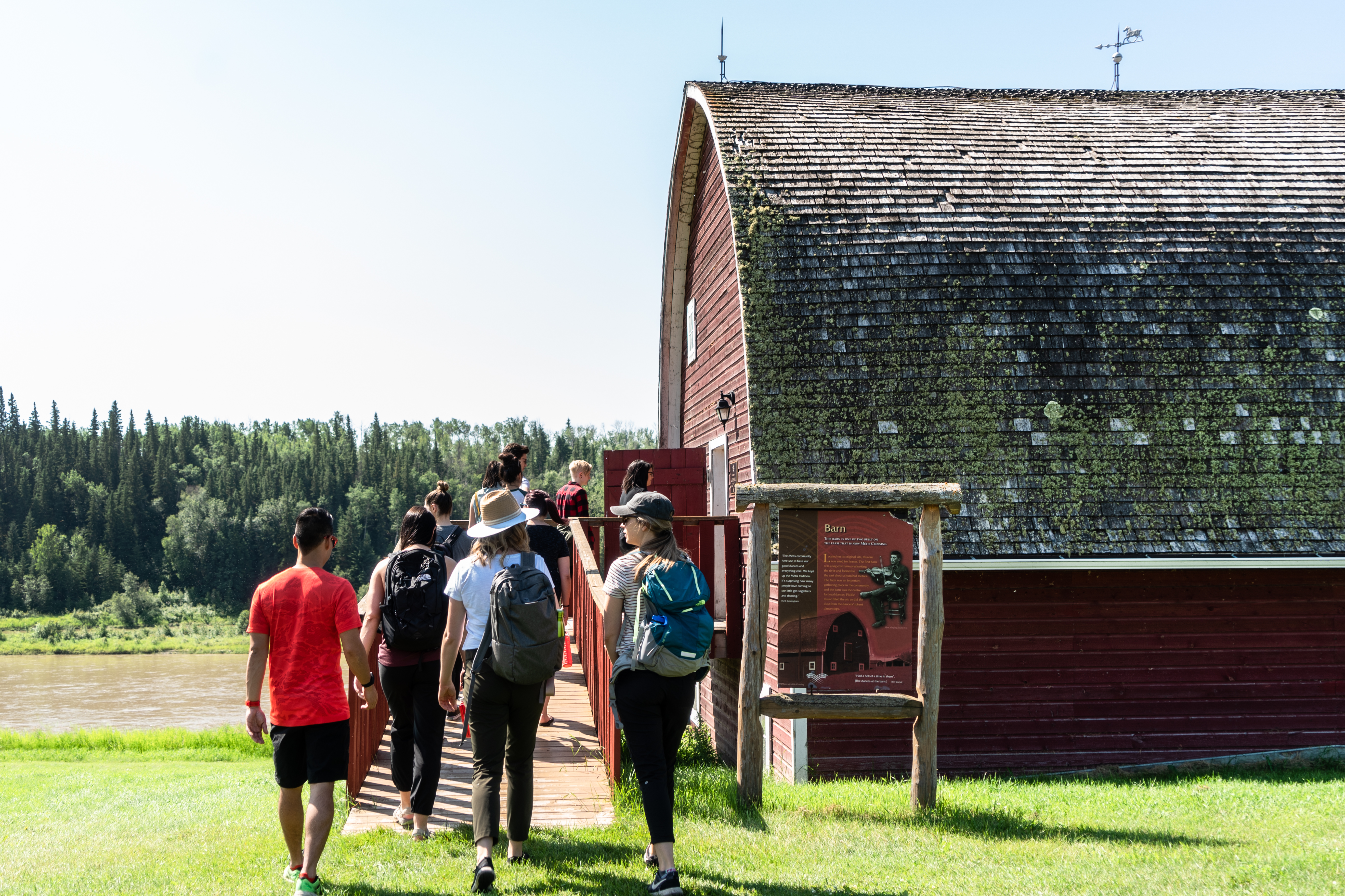 Metis Crossing A group of people enter a barn